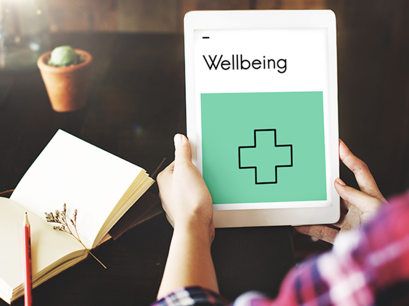Hands holding a tablet with the word wellbeing on it