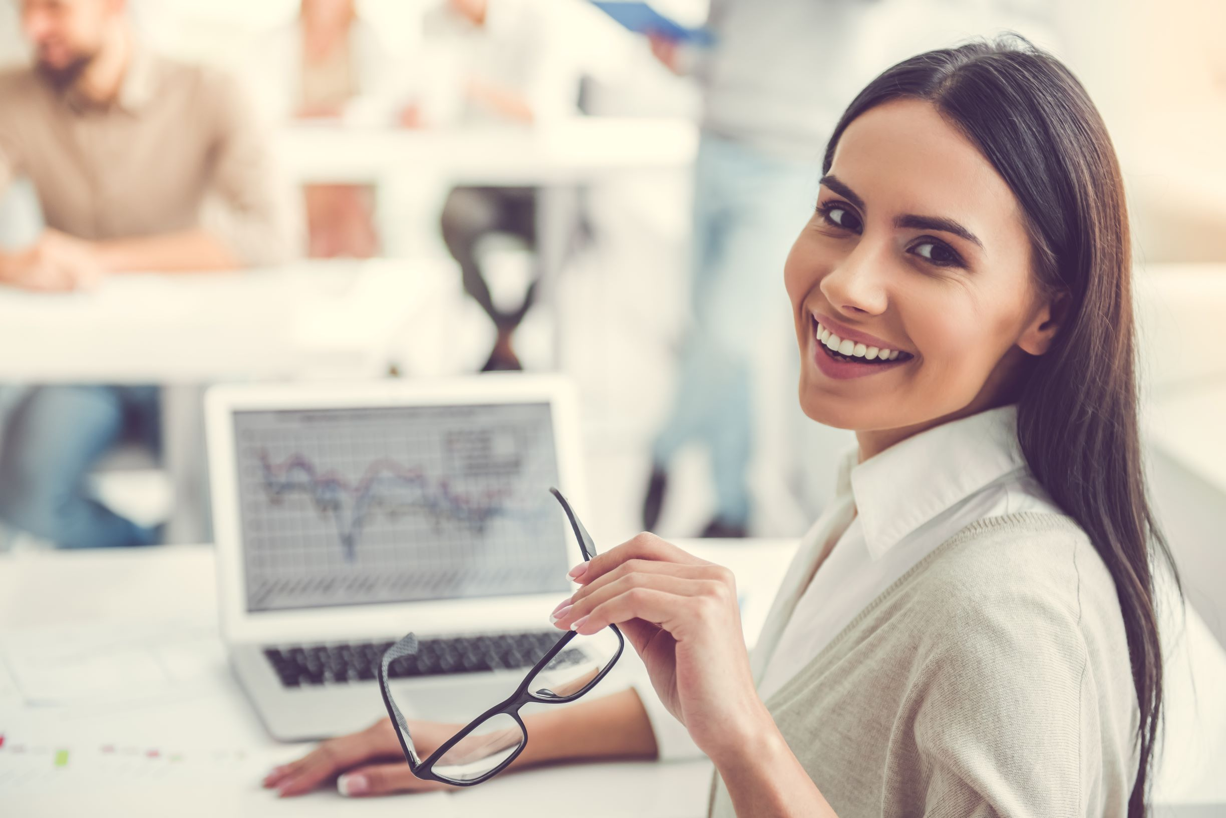 Smiling female employee working on laptop