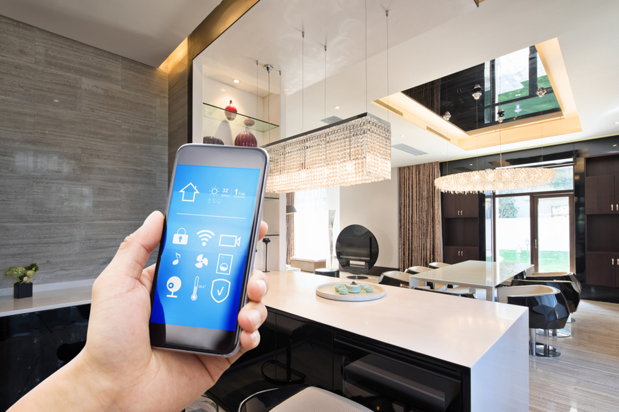 Hand holding a smartphone in a modern home setting